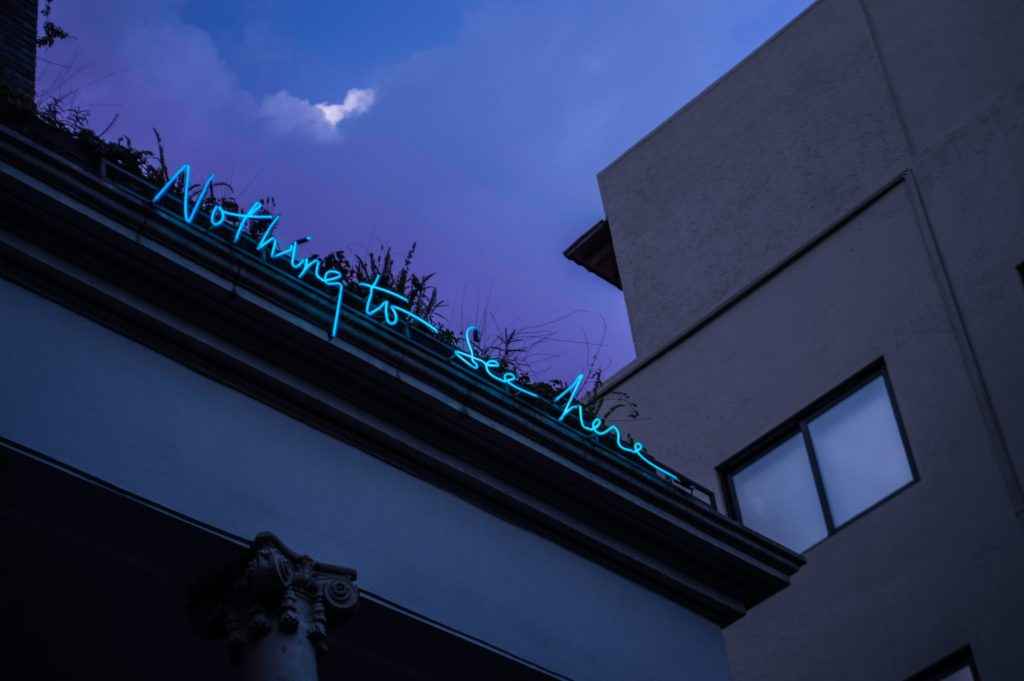 Façade d'un bâtiment disposant d'un écriture en néon. La scène est vu du bas et comporte un ciel violet.